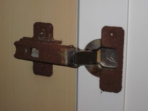 Bathroom cabinet hinge that has rusted.