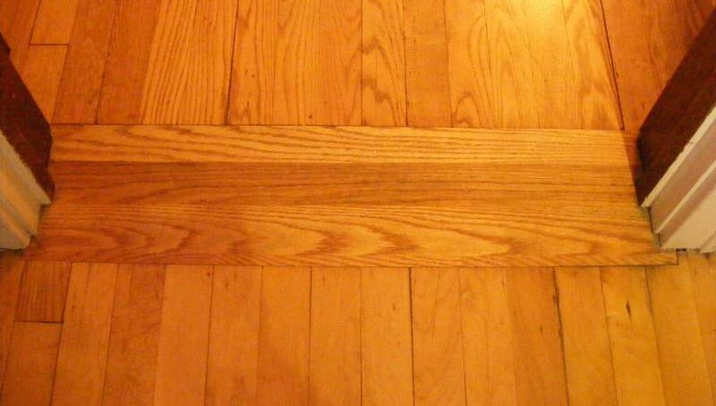 One piece of oak filling the gap between the kitchen and dining room floors.