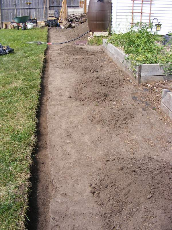 Vegetation cleared and lawn edging trench dug