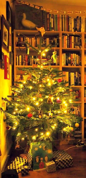 Christmas tree by bookshelves