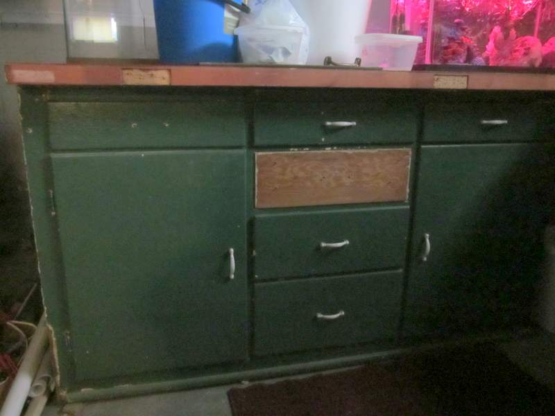 The cabinet in the basement covered in spare aquarium equipment.